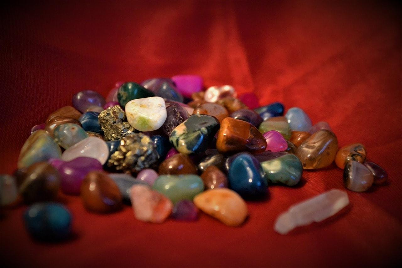 Kamienie szlechetne rozsypane na czerwonym tle.