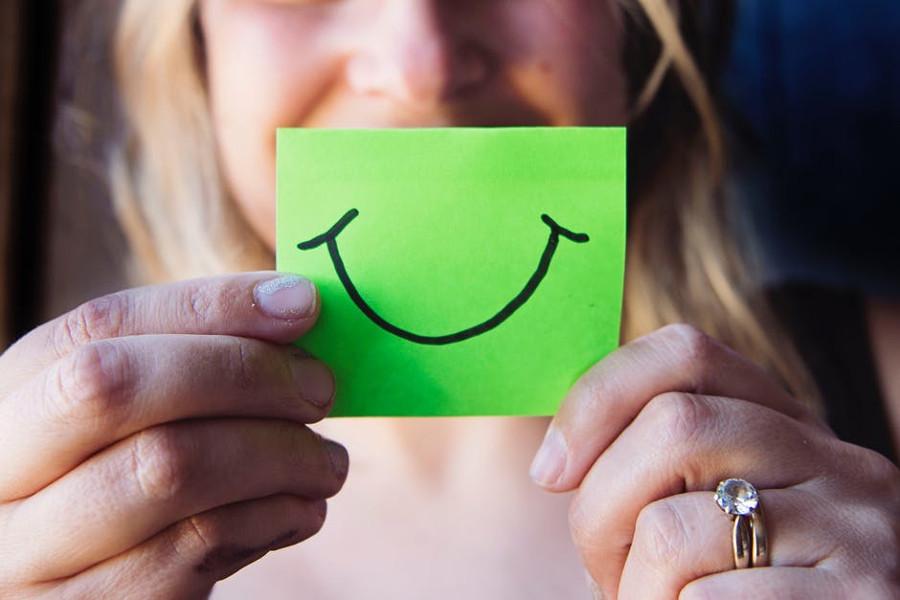ręce trzymające kartkę z narysowanym uśmiechem