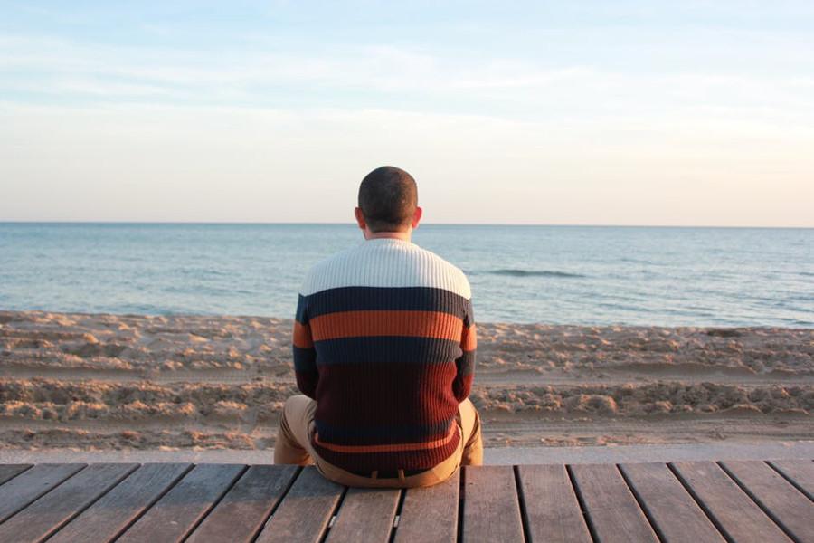 mężczyzna siedzący na plaży