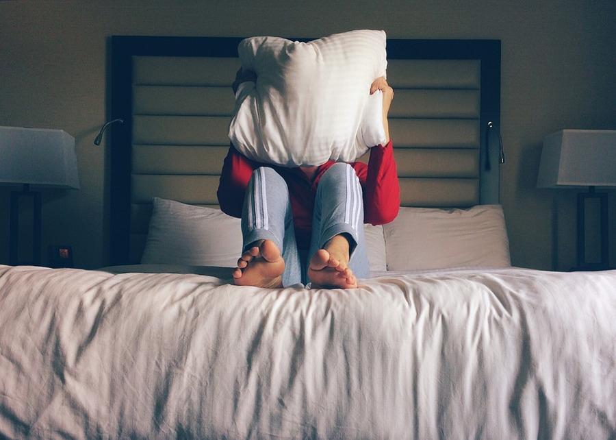 mężczyzna na łóżku, zakrywający się poduszką