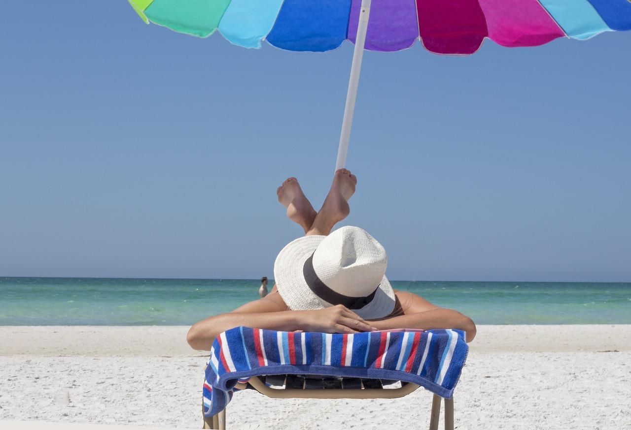 kobieta opalająca się na plaży pod parasolem