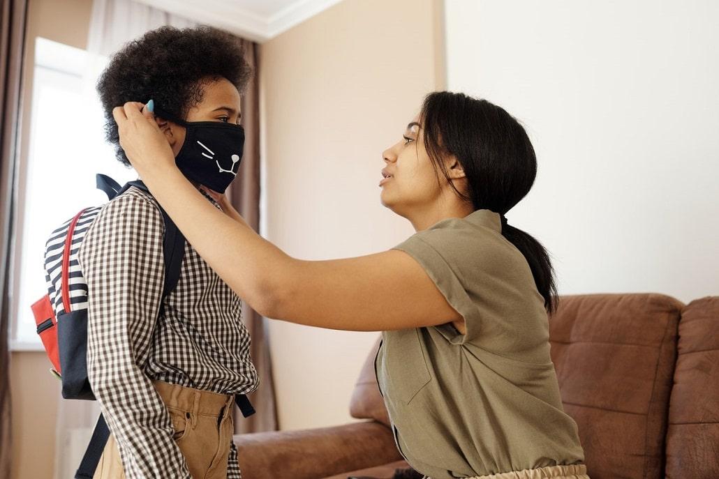Matka ubiera dziecku maskę przeciw koronawirusowi
