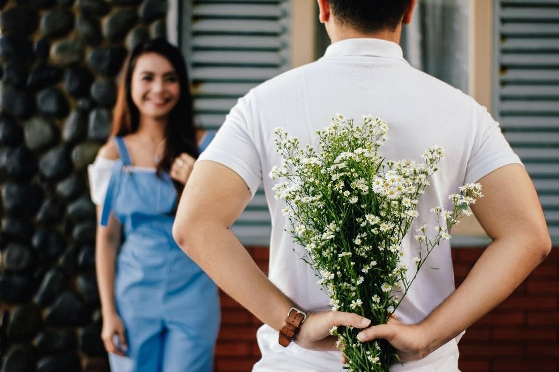 Mężczyzna schowa za plecami bukiet polnych kwiatów, które zamierza wręczyć stojącej przed nim ukochanej