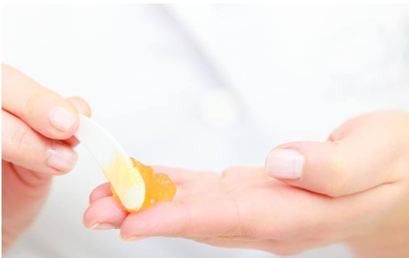 Kosmetyczka nakłada krem na dłoń