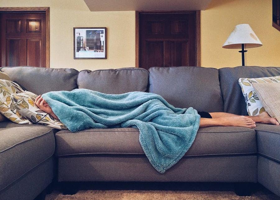 mężczyzna śpiący na sofie pod kocem