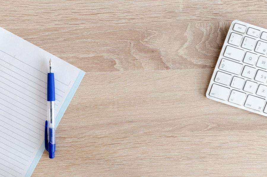 kartka z długopisem oraz laptop na biurku