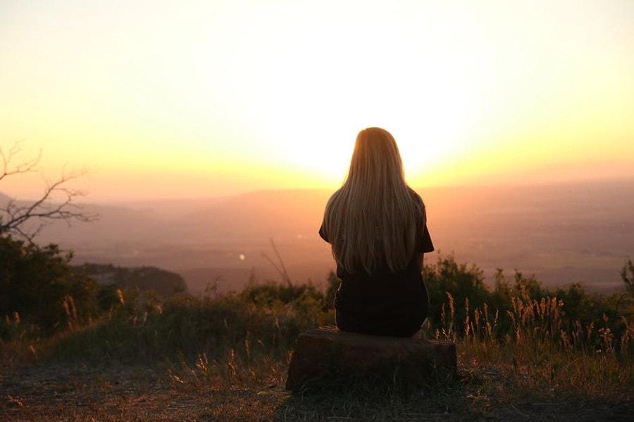 kobieta siedząca tyłem na tle zachodu słońca