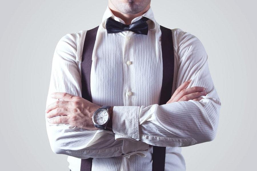 mężczyzna w koszuli z szelkami i muszką