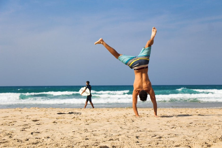 mężczyzna robiący gwiazdę na plaży
