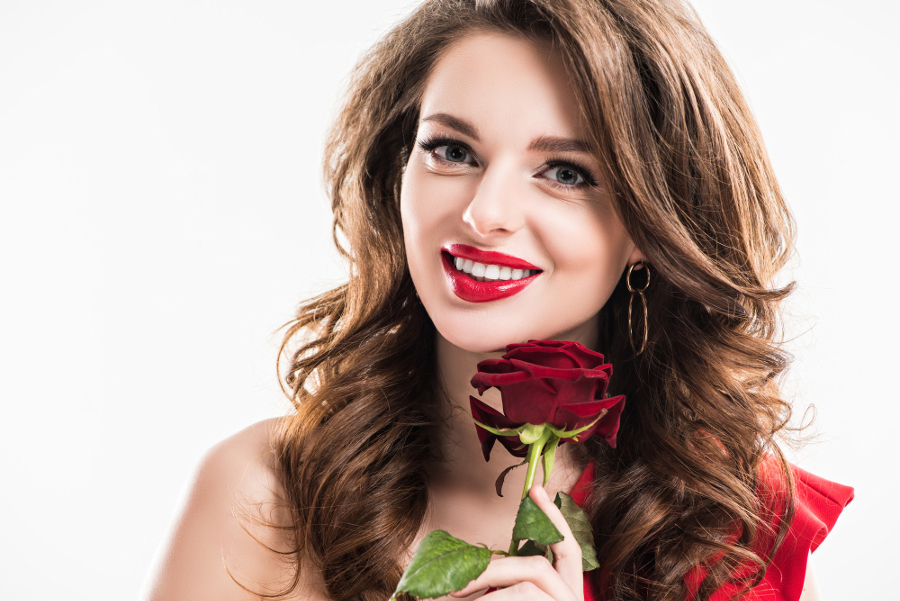 Kobieta w czerwonych ustach z różą w ręce
