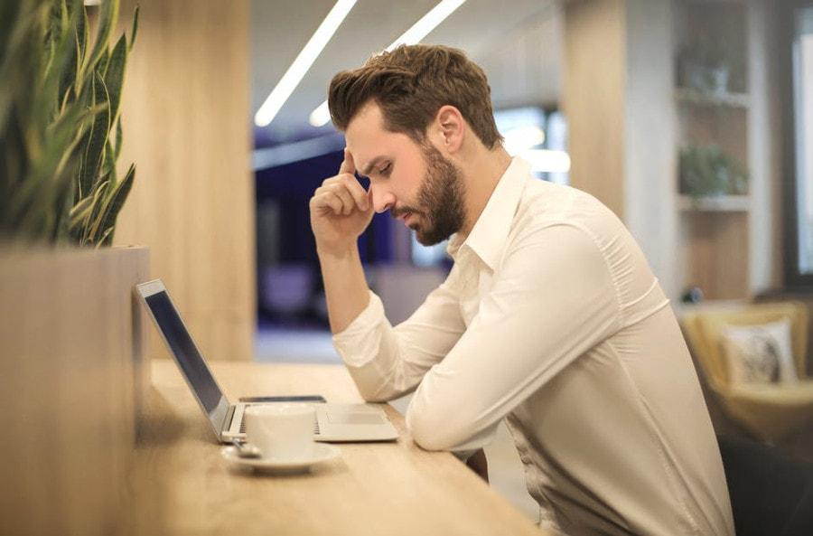zestresowany mężczyzna przy laptopie