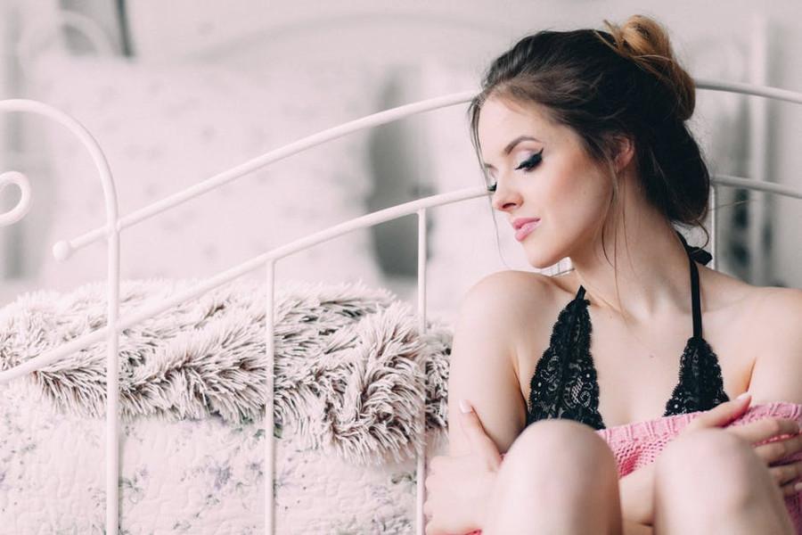 kobieta, która siedzi obok łóżka