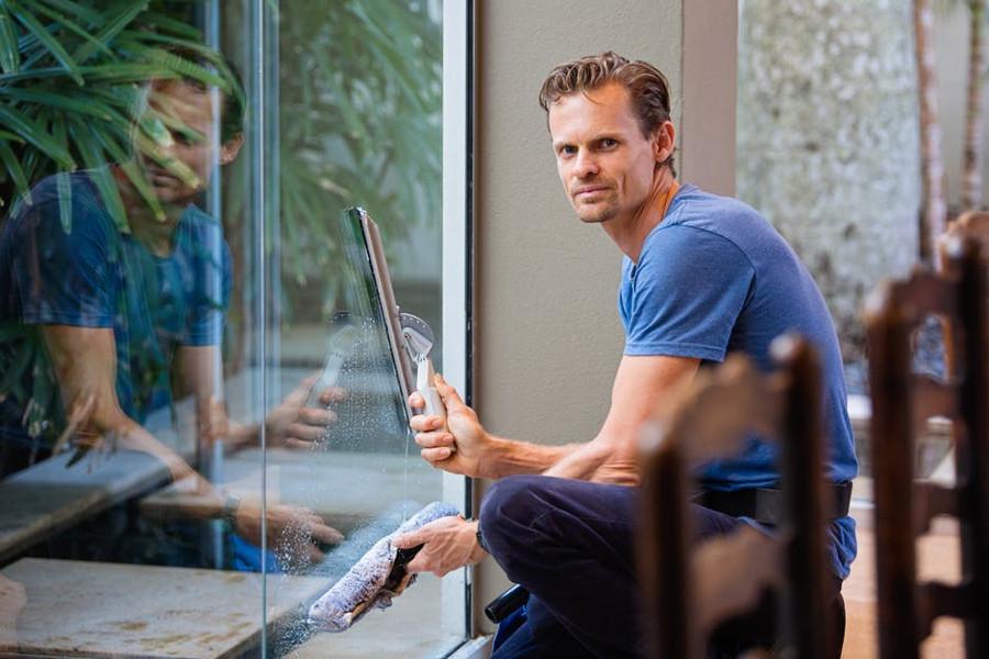 mężczyzna myjący okna
