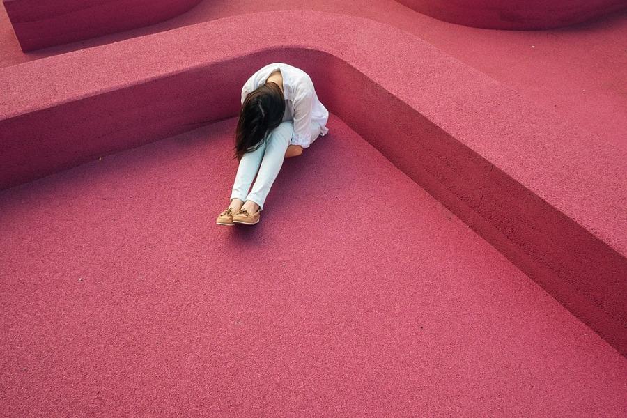 przgnębiona kobieta siedząca na podłodze