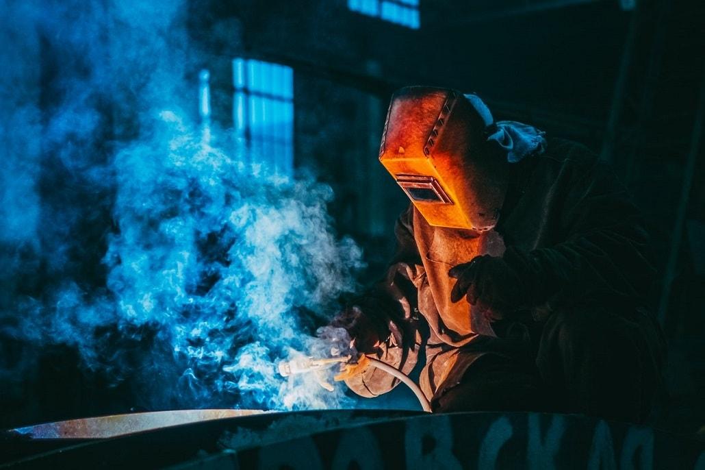 Spawacz spawa w kłębach dymu o niebieskim zabarwieniu.