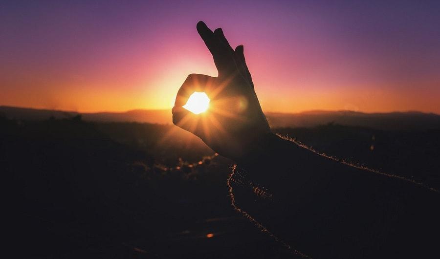 Dłoń chwytająca zachodzące słońce