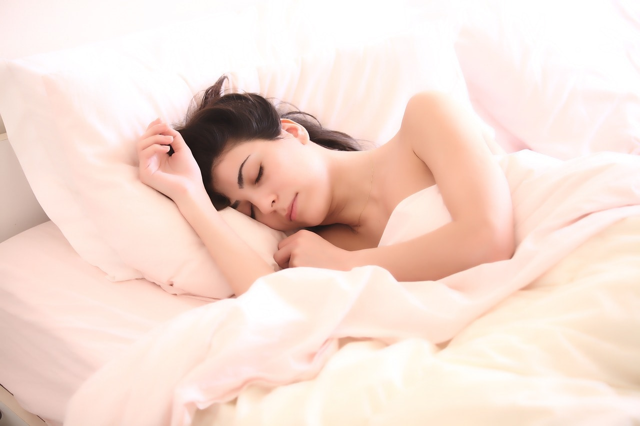 Kobieta smacznie śpiąca pośrodku bladoróżowej pościeli