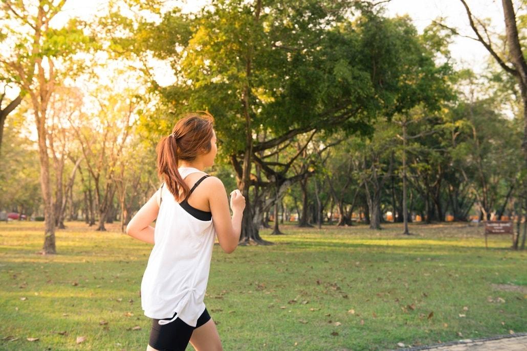 Kobieta biega po parku w słoneczny dzień
