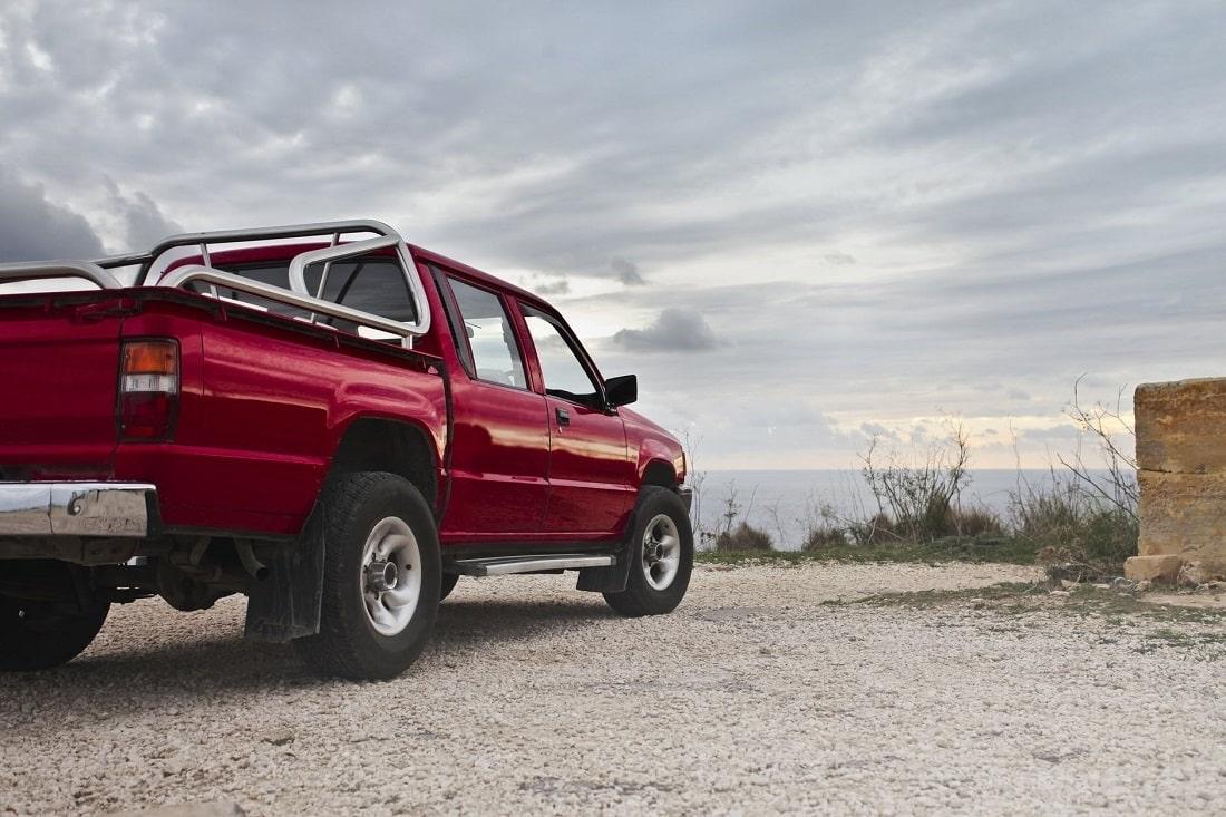 Czerwony samochód stojący na skraju ziemi przy morzu