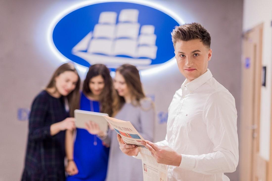 Uśmiechnięty, przedsiębiorczy student na tle logo Akademii Leona Koźmińskiego