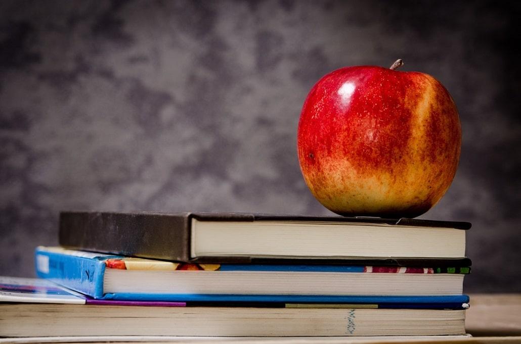 Jabłko leżące na książkach, symbol edukacji szkolnej
