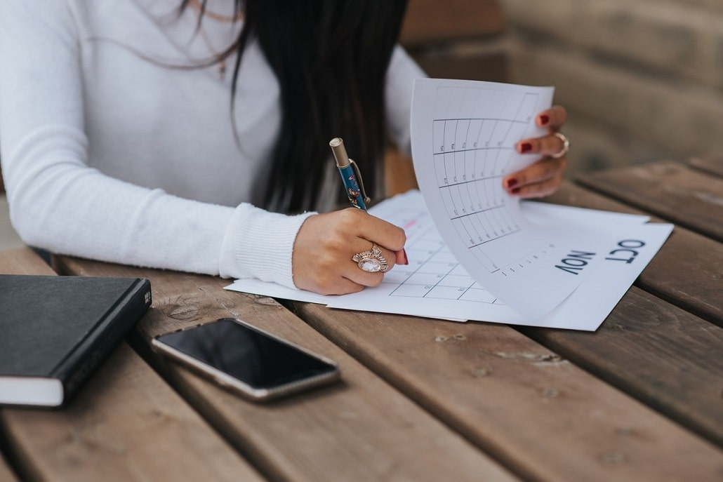 Kobieta wpisuje coś w kalendarz