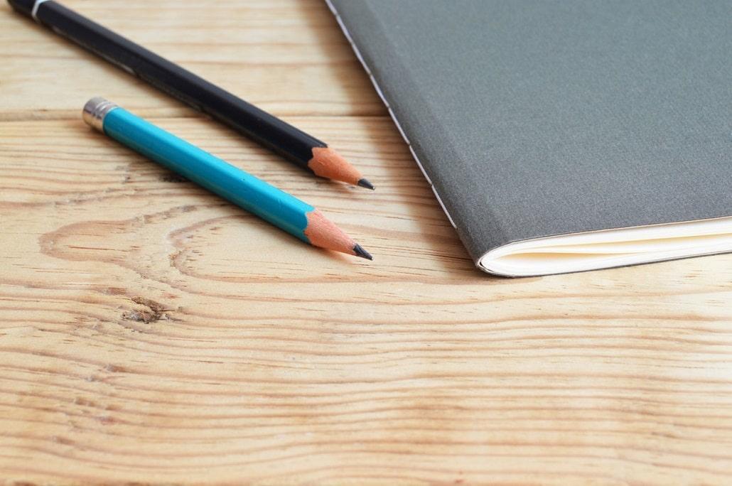 Ołówki obok zeszytu, symbol egzaminu