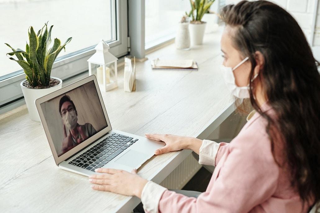 Kobieta w masce przed komputerem