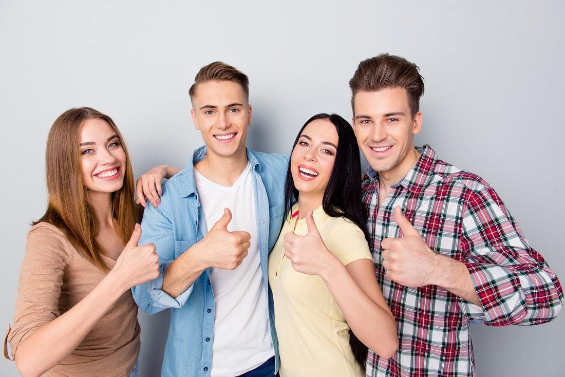 Młodzi ludzi pozują uśmiechnięcie do zdjęcia i pokazują OK