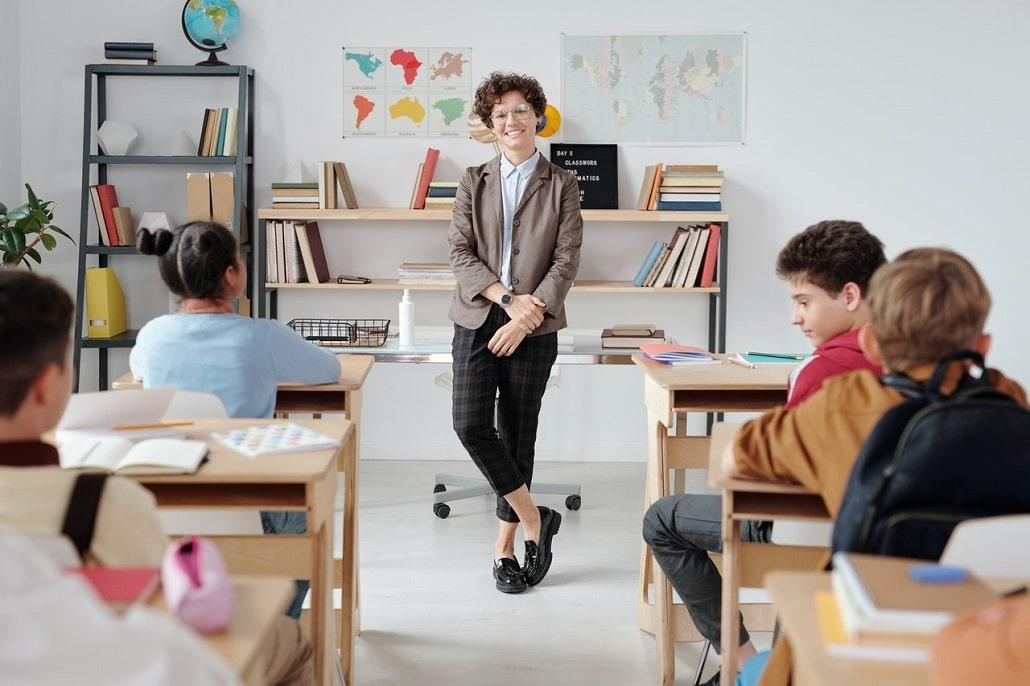 Nauczycielka w klasie pełej uczniów podczas zajęć stacjonarnych w szkole