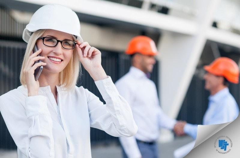 Kobieta w białym kasku na placu budowy, rozmawia przez telefon