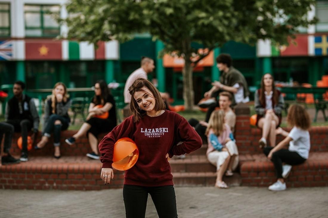 Młoda dziewczyna z piłką i bluzą Uczelni Łazarskiego