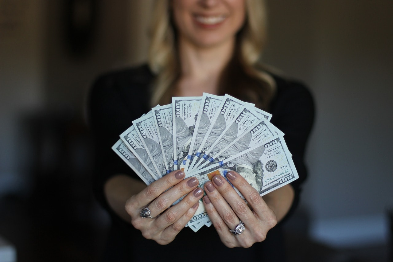 Kobieta trzymajaca plik banknotów
