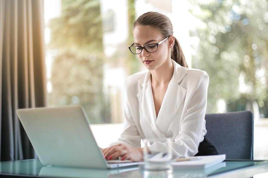 Młoda elegancka dziewczyna w pracy przed komputerem