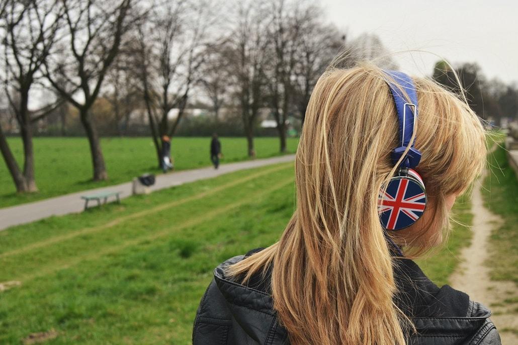 Dziewczyna ze słuchawkami na uszach. Słuchawki mają na sobie flagę Zjednoczonego Królestwa