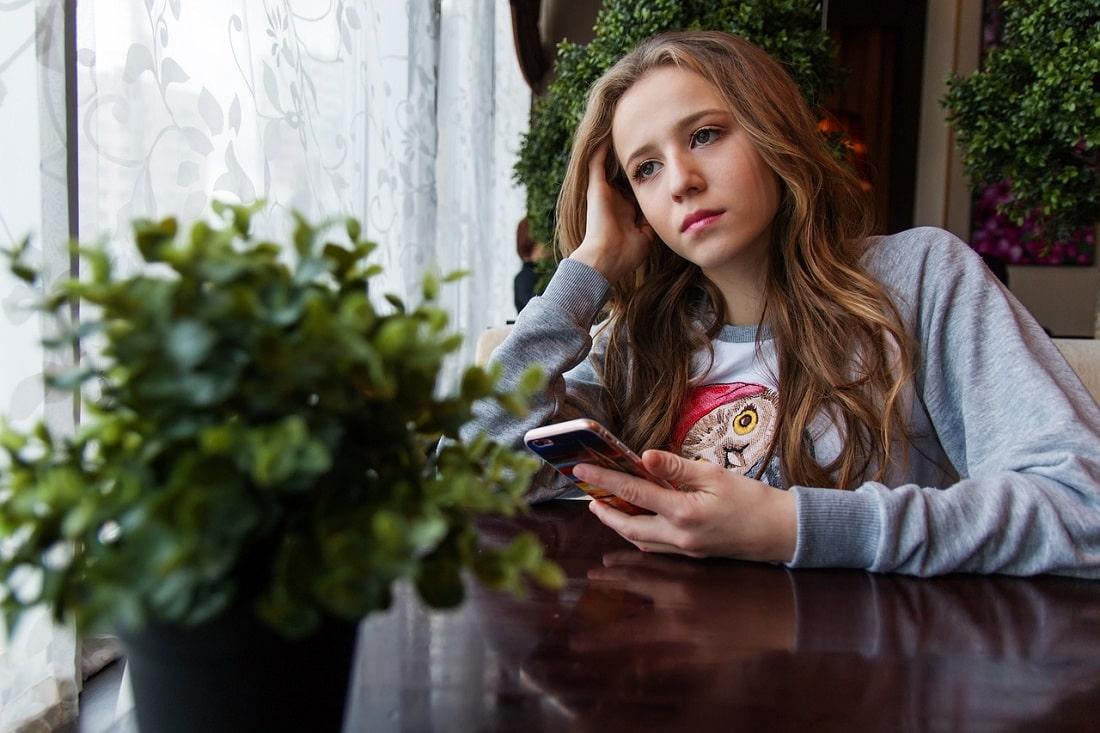 Znudzona studenta z telefonem w reku