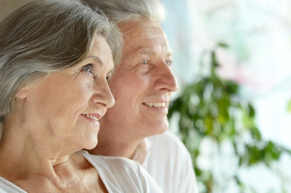 Starsza Pani i Starszy Pan uśmiechają sie patrząc w dal