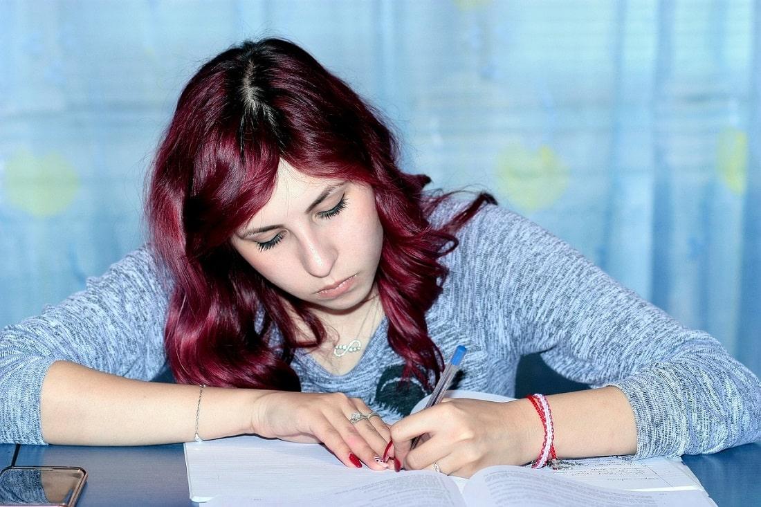 Młoda dziewczyna pisze coś w zeszycie
