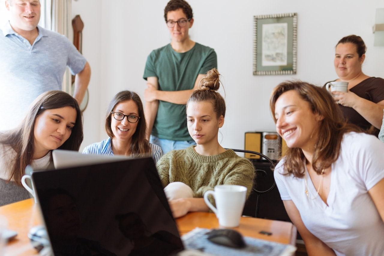 Młodzi ludzie siedzą przed komputerem i współpracują