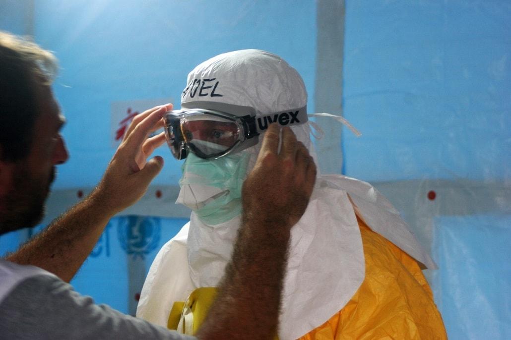 Człowiek w kombinezonie i masce przeci wirusom