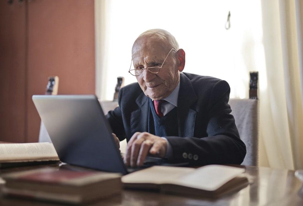 Starszy człowiek siedzi przed komputerem