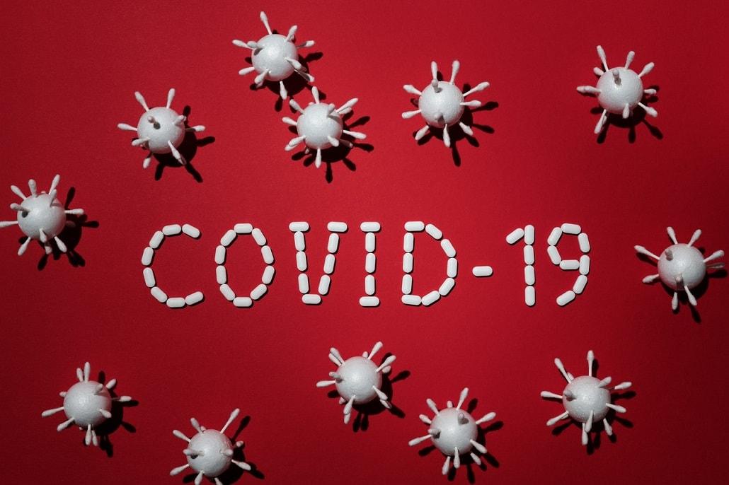 Napis COVID-19 otoczony wirusami