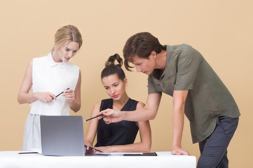 Młode osoby w pracy, dwie kobiety i mężczyzna patrząna laptopa