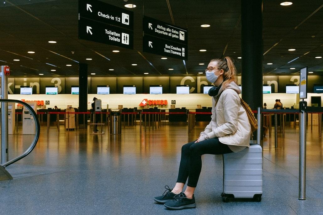 Kobieta w masce na lotnisku, czekanie na lot