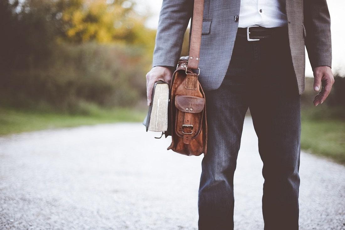 Młody człowiek z torbą i książką w ręku