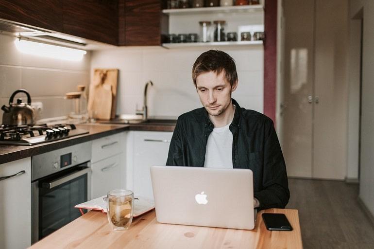 Młody mężczyzna przed komputerem, praca zdalna