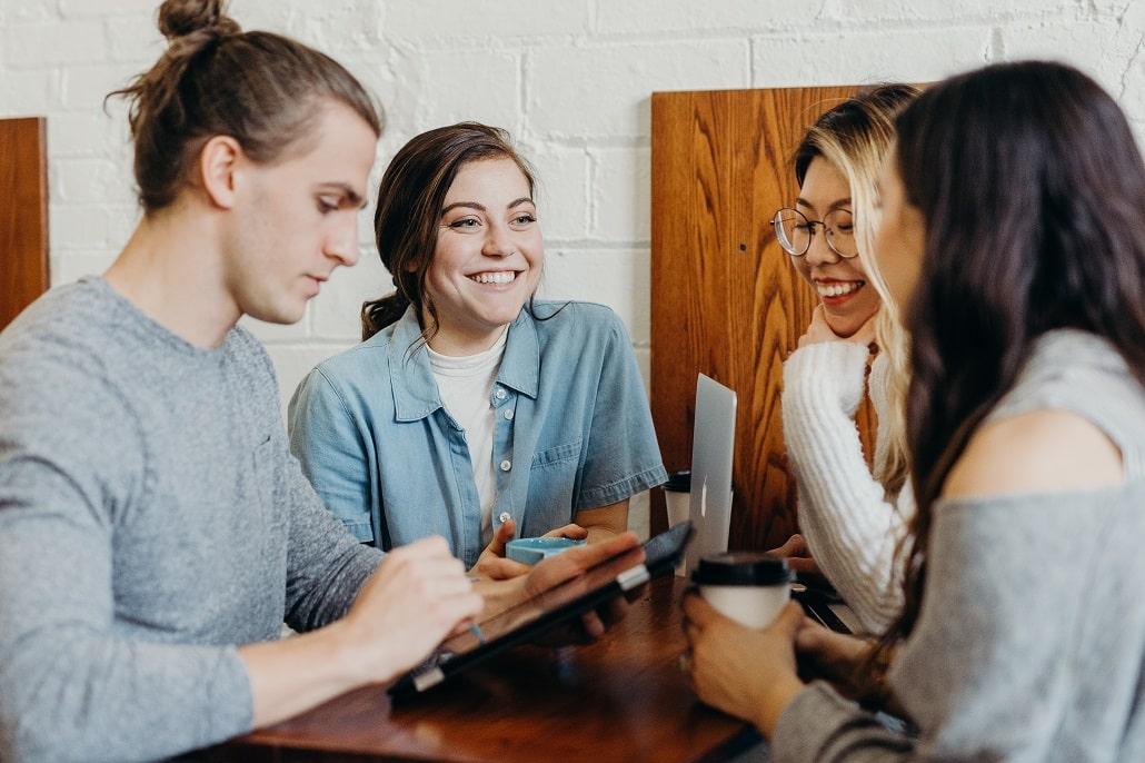 Młodzi ludzie przy stole, śmiech, spotkanie