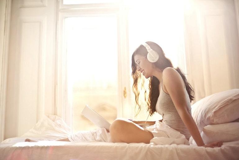 Młoda kobieta słucha muzyki siedząc na łóżku