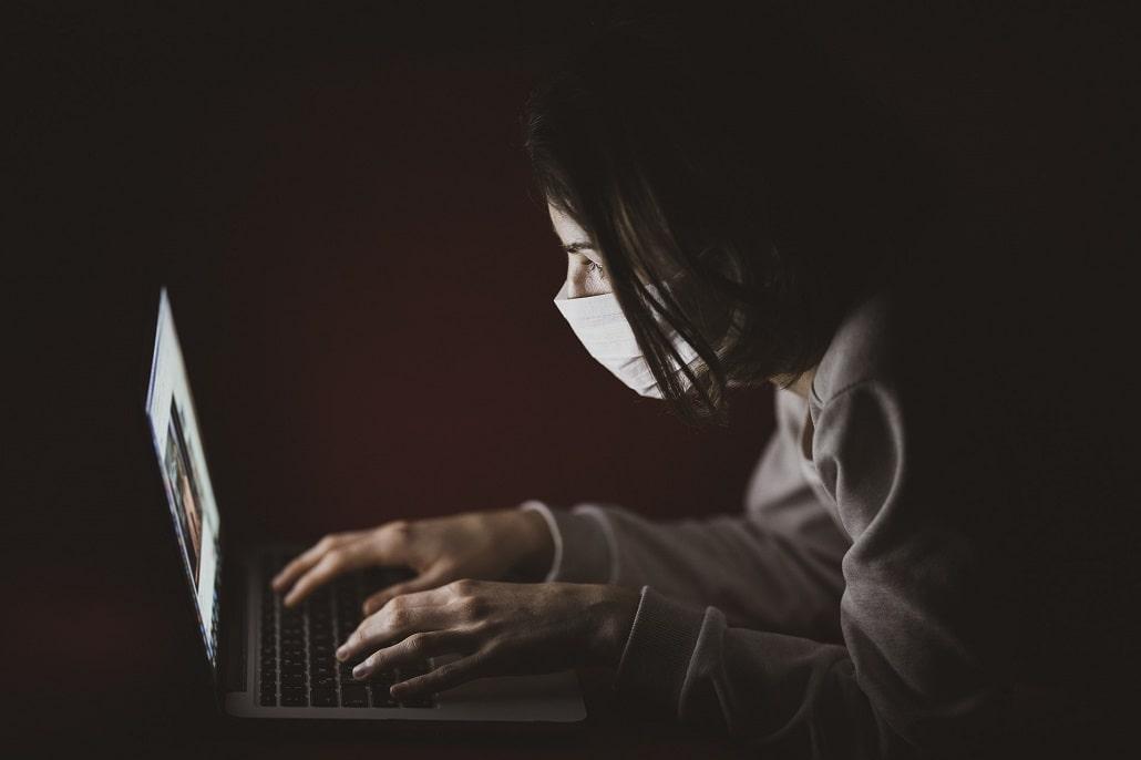 Ciemność, kobiet w masce przed ekranem komputera