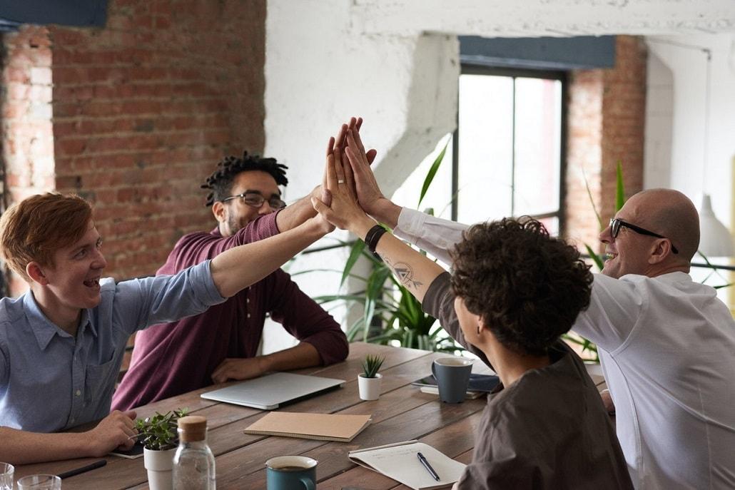 Czwórka ludzi w pracy przybija sobie piątki. Siedzą przy dużym stole.